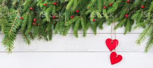 Dwa drewniane serca na tle gałązek choinki.