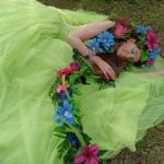 Na trawie leży piękna, ciemnowłosa dziewczyna w zielonej tiulowej sukni w kwiecistym wianku, którego przedłużenie wije się po ramionach aż na suknię.