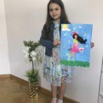 Na zdjęciu ciemnowłosa dziewczynka w kolorowej kwiecistej sukience trzyma w rękach autoportret w kwiecistym wianku, różowej spódniczce i rozwianych włosach