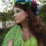 Profilowy portret ciemnowłosej dziewczyny w pięknym kwiatowym wianku. Dziewczyna ma wiosenny makijaż: zielone cienie na powiekach i zielone usta. W uszach ma własnoręcznie zrobione kolorowe wiszące kolczyki.